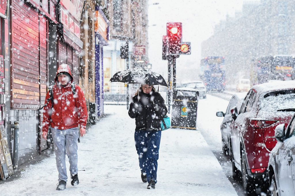 two people walking through the snow with an umbrella