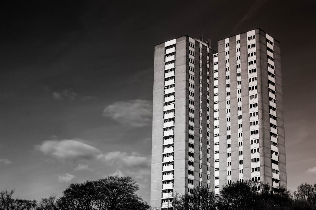 A black and white image of a large older tower block of flats