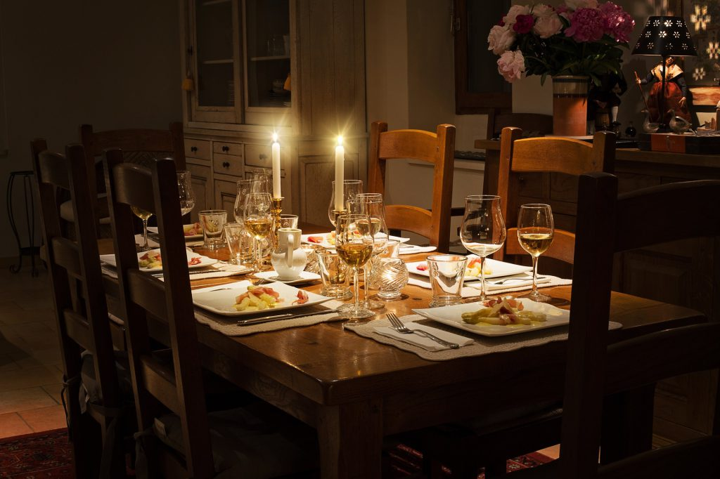 A table set for a family dinner with candles and wine. To demonstrate the potential risks of unattended candles.