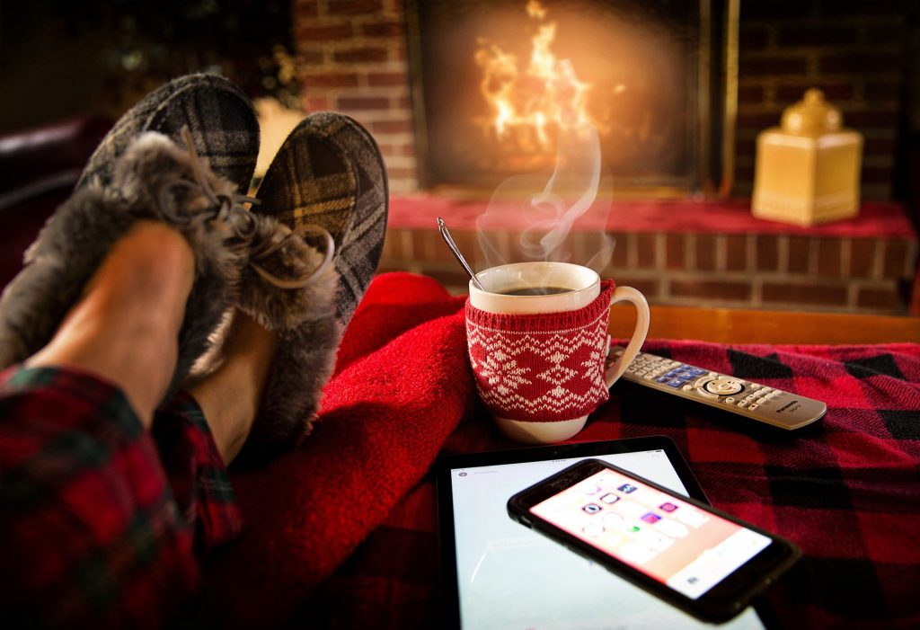Somebody wearing slippers with a hot cup of drink, chilled out by a cosy fire in their living room