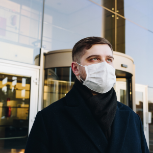 Man wearing a medical face mask standing outside of an office building