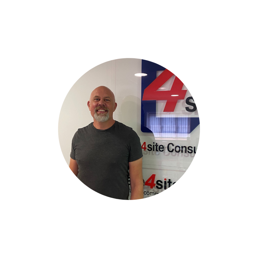 A photo of our new Health, Safety and Fire Advisor Ian- standing in our office in front of the 4site sign.